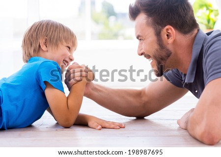 Little champion. Side view of happy father and son competing in arm wrestling while both lying on the hardwood floor  - stock photo