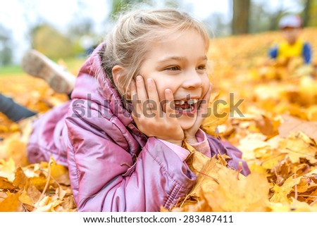 Little cheerful beautiful girl buried in autumn maple leaves yellow. - stock photo