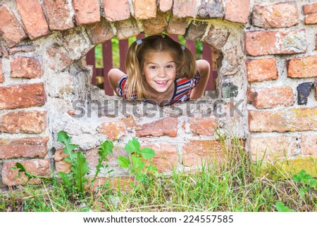 Little cheerful beautiful girl on ruins of an old brick building. - stock photo