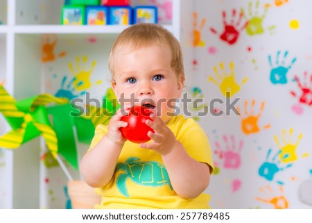 little cheerful child plays with a ball in the nursery - stock photo