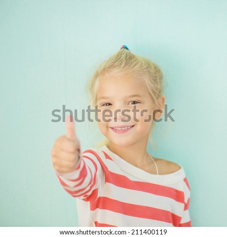 Little cheerful girl lifts thumb upwards, on green background.