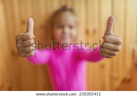 Little cheerful girl lifts thumb upwards, on wooden background. - stock photo