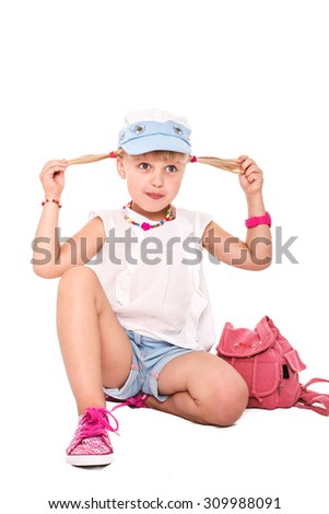 Little cheerful girl school girl in bright clothes with a grimace on his face on a white background isolated - stock photo