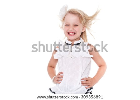 Little cheerful girl schoolgirl isolated on white background with blond hair developing - stock photo