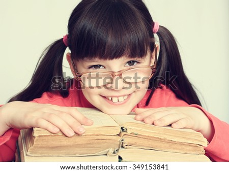 Little cheerful girl with glasses sitting on a pile of books.