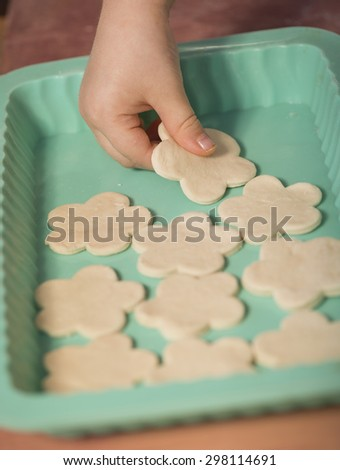 Little chef hands smeary with flour, putting the dough cut in flower shaped, in the baking tray - stock photo
