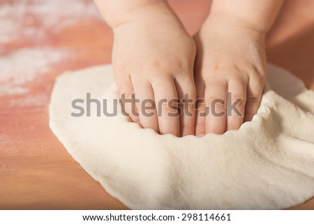 Little chef hands smeary with flour, putting the dough in the baking tray - stock photo