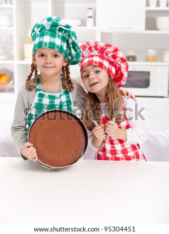 Little chefs baking a cake - smiling with cooking utensils in the kitchen - stock photo