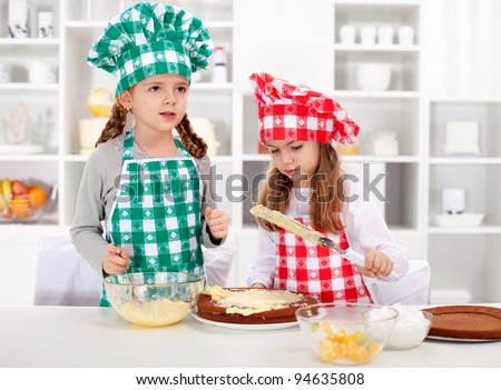 Little chefs making a cake - covering the layers with cream