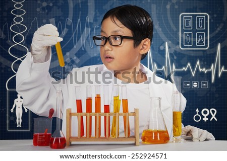 Little chemist doing experiment for healthcare with chemical fluid in the laboratory - stock photo