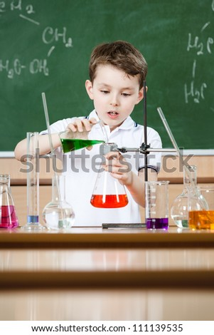 Little chemist holds scientific experiment - stock photo