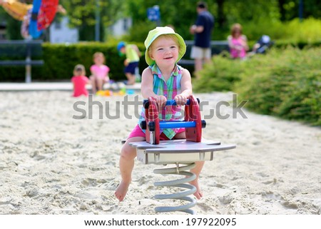 Little child, adorable blonde toddler girl, enjoying hot sunny summer day at the playground bouncing on spring horse - stock photo