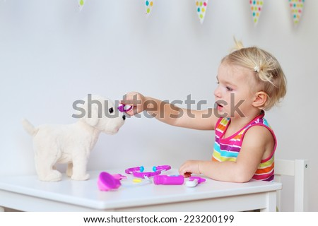 Little child, adorable blonde toddler girl, playing doctor role game and treating her puppy using her imagination and different medical tools - stock photo