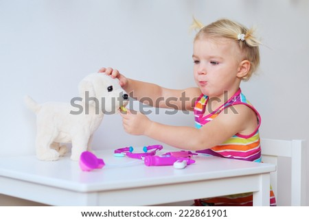 Little child, adorable blonde toddler girl, playing doctor role game with her puppy sitting at small white table in playroom at home, school or kindergarten - stock photo