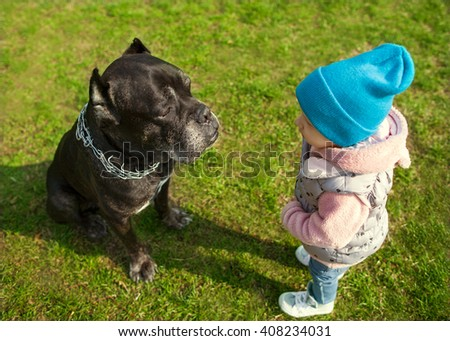 little child and dog are looking at each other playing on the grass, Cane Corso, psychological concept - stock photo