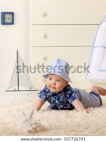 little child baby boy lying on the floor carpet indoors in baby room smiling hat clothing fashion - stock photo