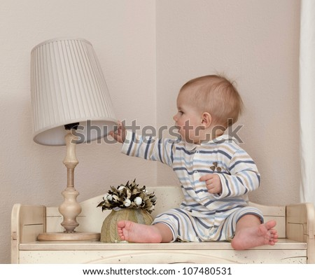 little child baby boy sitting  indoors in baby room with lamp - stock photo