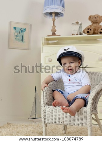 little child baby boy sitting on the chair indoors in baby room smiling happy fashion clothing