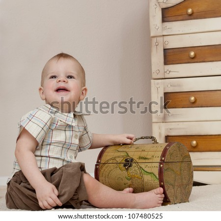 little child baby boy sitting on the floor indoors in baby room smiling happy - stock photo