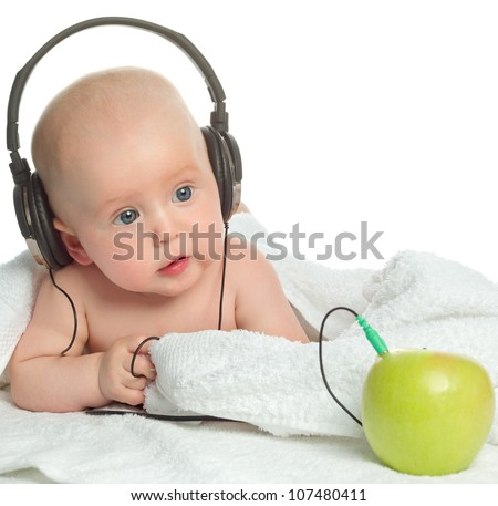 little child baby closeup portrait isolated on white studio shot face listening music headphones apple fruit - stock photo