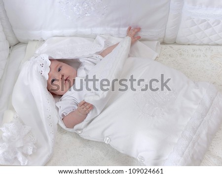 little child baby girl lying  in bed in white clothing