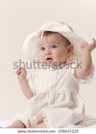 little child baby girl sitting on the floor indoors hat dress fashion