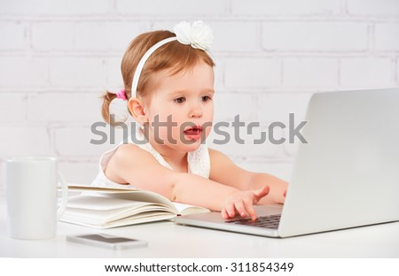 little child baby girl works at the computer at home - stock photo
