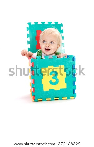 little child baby playing with numbers puzzles smiling isolated on white on white background studio shot learning counting 1 year sitting in the box - stock photo
