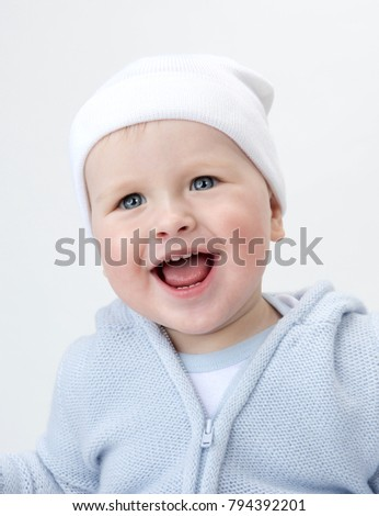 little child baby smiling closeup portrait isolated on white studio shot face positive happy wart sweater and hat