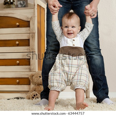 little child baby smiling making first steps - stock photo