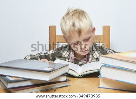 Little child blond focused student boy sitting at desk and reading/ studying open book, more books at table around, pile of books
