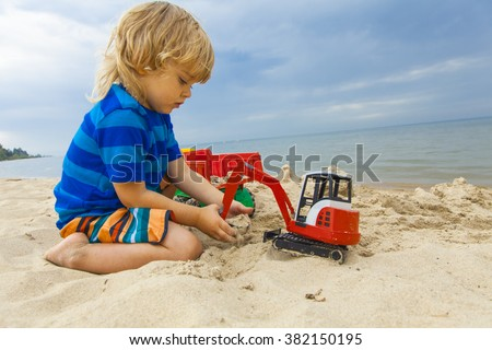 little child boy loads sand with the help of excavator toys on the beach - stock photo