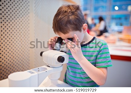 Little child boy looking through microscope in school