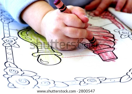 Little Child Coloring In Book With Crayons