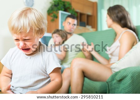 Little child crying due to a quarrel of parents - stock photo