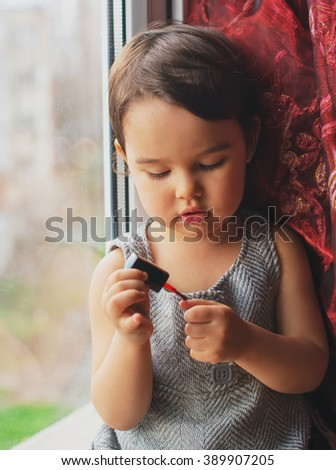 Little child, cute toddler girl having fun playing at home with colorful nail polish doing manicure - stock photo