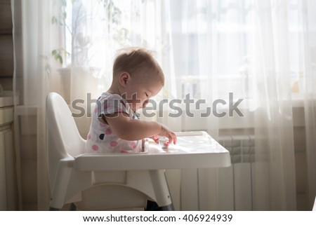 Little child, cute toddler girl having fun playing at home with her doll,playing with baby doll singing doll out of  cup, takes care of the doll, casual lifestyle photo series in real life interior, - stock photo