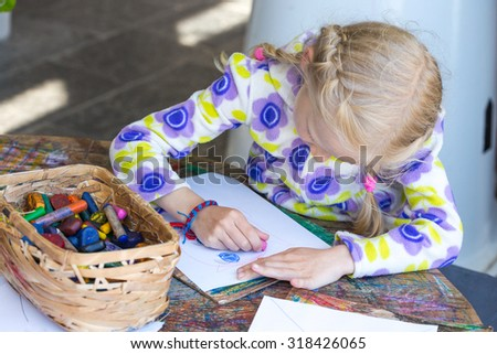 little child drawing a pastel on paper  - stock photo