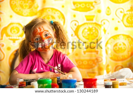 Little child, drawing paint with paint of face - stock photo