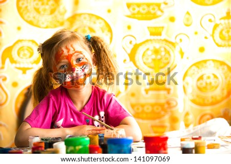 Little child drawing paint with paint of face. - stock photo