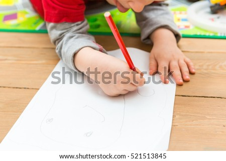 Little child drawing with pencil on white paper. Close up of toddler playing on floor.