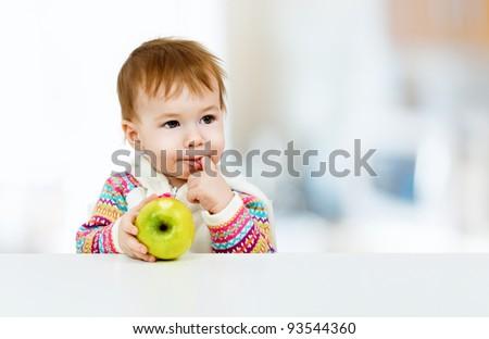 little child eating green apple - stock photo