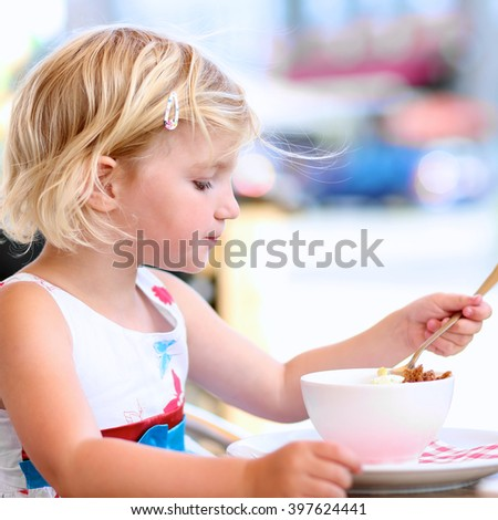 Little child eating ice-cream in cafe. Adorable blonde toddler girl enjoying delicious refreshing dessert on sunny summer day. - stock photo