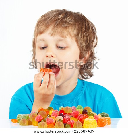 Little child eating jelly candies on a white background - stock photo