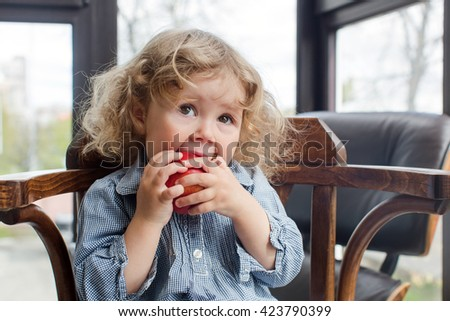 little child eating red apple indoors - stock photo