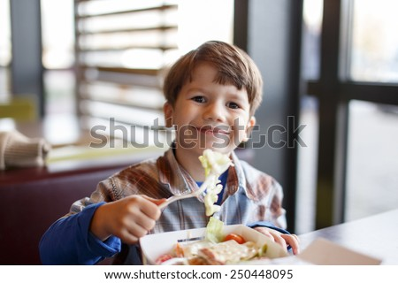 Little child eating salad in fast food restaurant - stock photo