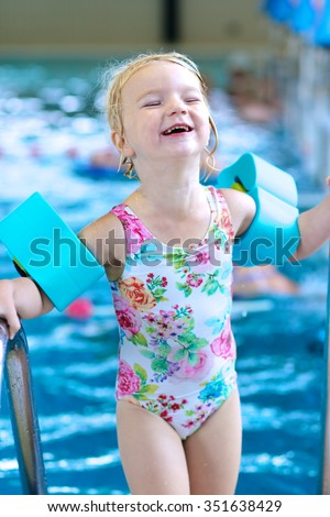 Little child enjoying swimming pool. Cute toddler girl wearing colorful swimsuit and armbands having fun in the water. Adorable sportsman kid promoting healthy lifestyle. - stock photo