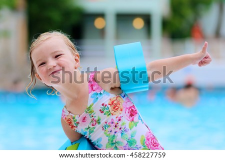 Little child enjoying swimming pool. Cute toddler girl wearing colorful swimsuit and armbands having fun in water park. Kid showing thumb up promoting healthy lifestyle. - stock photo