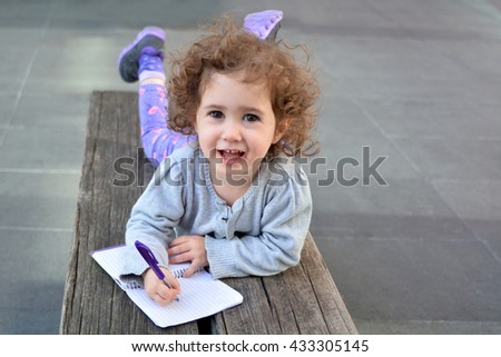 Little child (girl age 2) write with a pen on a notebook. Real people concepts and ideas,  copy space - stock photo
