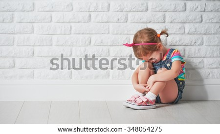 little child girl crying and sad about an empty brick wall - stock photo